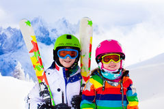 Ski and snow fun for kids in winter mountains. Kids skiing in mountains. Active children with safety helmet, goggles and poles. Ski race for young kids. Winter Royalty Free Stock Images