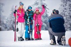 Ski, snow sun and fun - father taking picture of family on snow stock photo