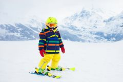 Ski and snow winter fun for kids. Children skiing. Child skiing in the mountains. Kid in ski school. Winter sport for kids. Family Christmas vacation in the Alps stock images