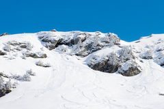 Ski snowboard and avalanches tracks. Mountain slopes with rocky outcrops, trees and signs of ski, snowboard and avalanches in the resort of Les Menuires, France Stock Photography