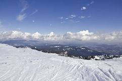 Ski and snowboard slope. Top of the ski and snowboard slope with some clouds in the sky Stock Photo