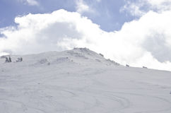Ski and snowboard slope. Top of the ski and snowboard slope with some clouds in the sky Stock Image