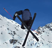 Ski Stunt Jump. A Freestyle ski jumper performs a tele-heli stunt with crossed skis, high in the air Stock Photos