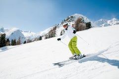 Ski, sun and fun. Mid adult woman skiing downhill Stock Photos