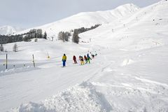 A ski teacher and kids learning skiing in the ski piste in the alps switzerland.  Stock Photos