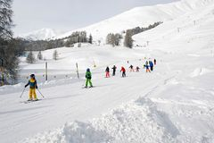 A ski teacher and kids learning skiing in the ski piste in the alps switzerland.  Stock Photography