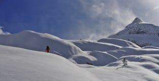 Ski touring in British Columbia. Skier skinning up a bumpy slope of snow, towards a sharp peak Stock Photo
