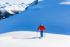 Ski touring man reaching the top at sunny day. Royalty Free Stock Image