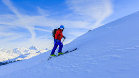 Ski touring man reaching the top at sunrise. royalty free stock images