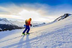 Ski touring man reaching the top at sunrise. stock images