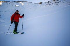 Ski touring man reaching the top at sunrise. royalty free stock photo