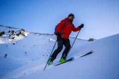 Ski touring man reaching the top at sunrise. stock photo