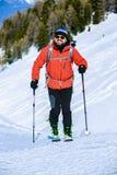 Ski touring man reaching the top at sunrise. stock photos