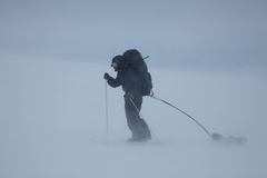 Ski touring man with sled in bad weather Stock Photography