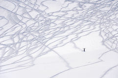 Ski traces and a small figure of freeride skier. Ski traces on snow powder and small figure of free-ride skier happily rising hands Royalty Free Stock Image