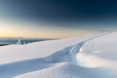 Ski Tracks. Sunrise with the last of the stars, In the mountains, fresh snow with ski touring tracks. Location Kaikoura, New Zealand Royalty Free Stock Photo