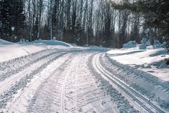 Ski trail in the forest. Traasa in the winter forest. The road for walking through the winter forest. Taiga in the winter. Tracks. From the snowcat. Footprints stock photo