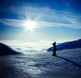 Ski traveler woman in winter mountains landscape. Ski traveler woman silhouette in amazing winter mountains landscape, over the clouds, opposite to sunset sky Royalty Free Stock Image