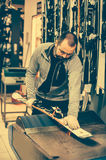 Ski tuning and reapairs. Winter shop worker doing base repair Royalty Free Stock Photography
