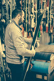 Ski tuning and repair. Winter shop worker doing base repair Royalty Free Stock Photography