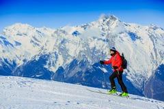 Ski voyageant l'homme atteignant le dessus dans les Alpes suisses Image stock
