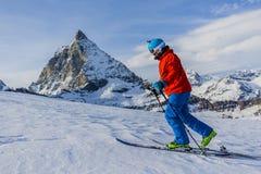 Ski voyageant l'homme atteignant le dessus dans les Alpes suisses Photo stock