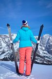 Ski, winter, snow, skiers, sun and fun. Back view of Middle Aged Woman On Ski Holiday In Mountains Royalty Free Stock Photo