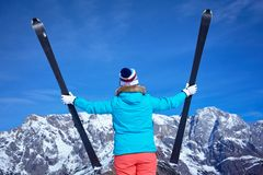 Ski, winter, snow, skiers, sun and fun. Back view of Middle Aged Woman On Ski Holiday In Mountains Royalty Free Stock Image