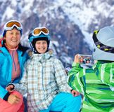 Ski, winter, snow, skiers, sun and fun. Boy photographed family on phone during winter vacations Stock Photo