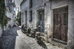 Small streets of Skiathos. Skiathos, Greece – June 25th 2015: Narrow cobbled street with motorcycles at Skiathos Royalty Free Stock Images