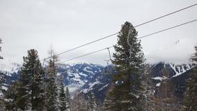 Skiaufzug auf einem Hintergrund von Schnee-mit einer Kappe bedeckten Bergen Leere Stühle bewegen sich gegen den Hintergrund eines stock video