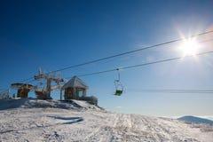 Skiaufzug zum Winterberg auf blauem Himmel im Sonnenschein lizenzfreie stockbilder