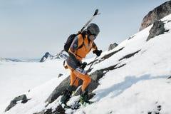Skibergsteiger, der auf Felsen mit den Skis gegurtet zum Rucksack klettert Lizenzfreie Stockfotos