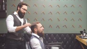 Skicklig barberare Ung man som får en gammalmodig rakning med den raka rakkniven stock video