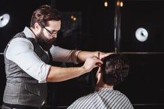Skicklig barberare Ung man som får en gammalmodig rakning med den raka rakkniven arkivfoton