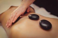 Skicklig kosmetolog som genomgår massagen för kvinna Arkivfoton