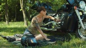 Skicklig kvinnlig cyklist som reparerar den utomhus- motorcykeln