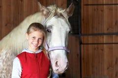 Skicklig ryttarinna med hans häst i stallet sport royaltyfri fotografi
