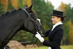 Skicklig ryttarinnajockey i enhetligt med hästen Arkivbilder