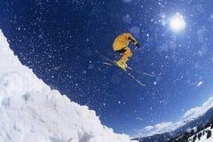 Skidåkare i ovannämnd snö för midair arkivfoto