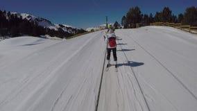 Skidåkare klättrar berget som rymmer repet med hans händer lager videofilmer