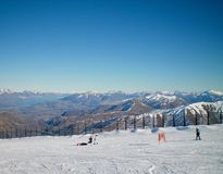 Skidåkare mot en bakgrund av berg Arkivfoto