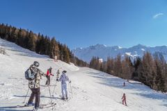Skidåkare och snowboarders i berg skidar lutningar av semesterortLes bågar, Frankrike Arkivbilder