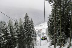 Skidåkare och snowboarders klättrar upp lutningen på en six-seaterstolelevator i dentäckte skogen royaltyfria bilder