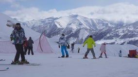 Skidåkare och snowboarders på skidar semesterorten, sikten på snöig berg för en vinter och skidlift stock video