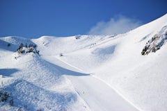 Skidåkare och snowboarders som rider på en skida, sluttar Arkivfoto