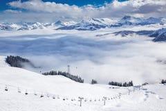Skidåkare på skidlift som tycker om sikten till dimmiga fjällängar i Österrike och härligt snöig land arkivfoton