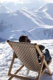 Skidåkare på vinterberg som vilar på sol-dagdrivare på den trevliga soldagen Fotografering för Bildbyråer