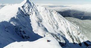 Skidåkare som står på ett korkat berg 4k för snö arkivfilmer