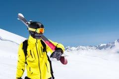 Skidåkareanseende på en lutning Mannen i en ljus dräkt, hjälmen och maskering i skidåkning ska skida I denkorkade bakgrunden royaltyfri foto